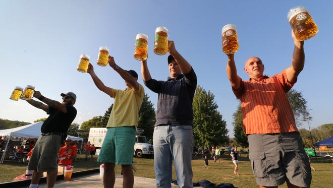 Competitors line up and hoist full litres of beer in a round of Masskrugstemmen, a German endurance game,  during Elm Grove's Oktoberfest hosted by the Elm Grove Foundation at Village Park on Sept. 23.