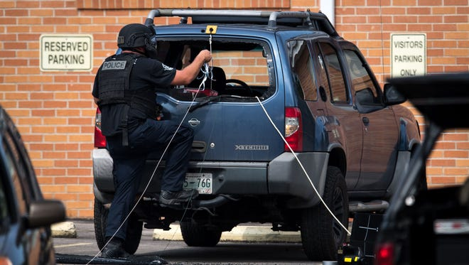 Police use rope and pulleys to remove items from the suspect's car following a shooting Sept. 24, 2017, at Burnette Chapel Church of Christ in the Nashville neighborhood of Antioch. A gunman killed one and wounded seven.