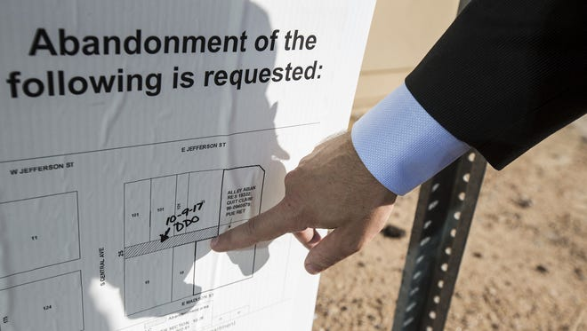 Sean Sweat points to the abandonment-appeal hearing sign in the alley behind the historic Barrister Building on the southeast corner of Central Avenue and Jefferson Street on Oct. 18, 2017, in Phoenix. The Phoenix City Council voted to close the alley.