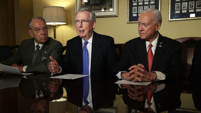 Senate Majority Leader Mitch McConnell speaks alongside Senate Finance Chairman Orrin Hatch and Sen. Chuck Grassley during a meeting with members of the Senate Finance Committee on Nov. 9.