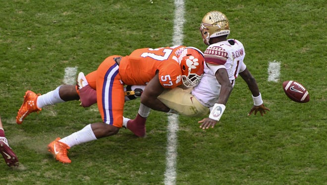 Clemson linebacker Tre Lamar (57) hits Florida State quarterback James Blackman (1), forcing a fumble during the first quarter in Memorial Stadium at Clemson on Saturday.