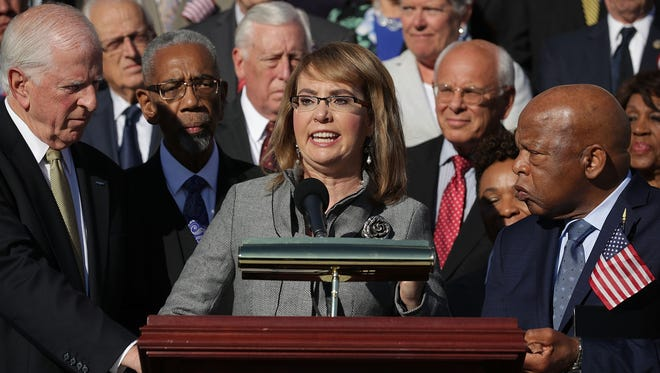 Former Congresswoman and gun violence victim Gabby Giffords (C) is joined by Rep. Mike Thompson (D-CA) (L), Rep. John Lewis (D-GA) and dozens of fellow Democrats during a rally on the East Front steps of the U.S. House of Representatives October 4, 2017 in Washington, D.C.