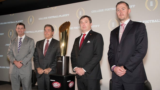 The two men standing closest to the College Football Playoff championship trophy, Kirby Smart, second from right, of Georgia and Nick Saban, of Alabama will be back in Atlanta for Monday night's national title game.