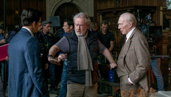 Mark Wahlberg, left, and Christopher Plummer, right, listen to director Ridley Scott during reshoots of 'All The Money In The World.'