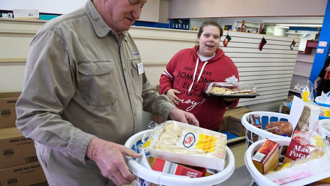 Christian Community Outreach volunteer Larry Butler helps Taylor Merino Wednesday with her Christmas basket as the organization distributed 119 Christmas baskets with $4,865 collected from the community.