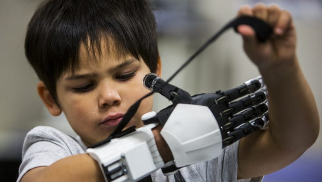 Jacob Taggart, 5, tests out his new prosthetic hand at the MORE Foundation on Friday, Dec. 22, 2017 in Phoenix. The nonprofit customized the prosthesis to look like a Stormtrooper's arm because Taggart is a Star Wars fan.