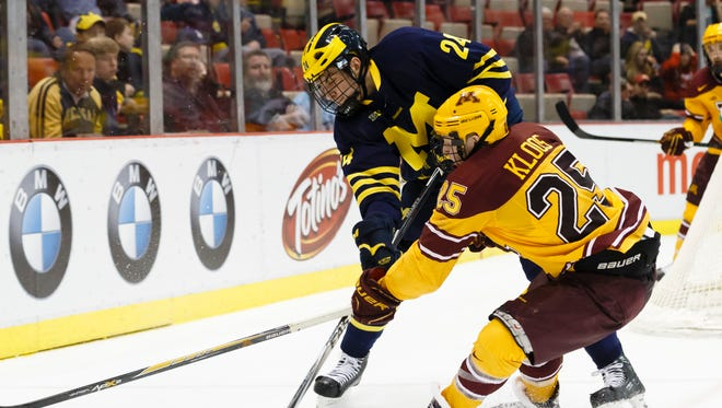 Michigan's Kevin Lohan and Minnesota's Justin Kloos battle for the puck in the third period in the Big Ten Conference tournament March 21, 2015 in Detroit.