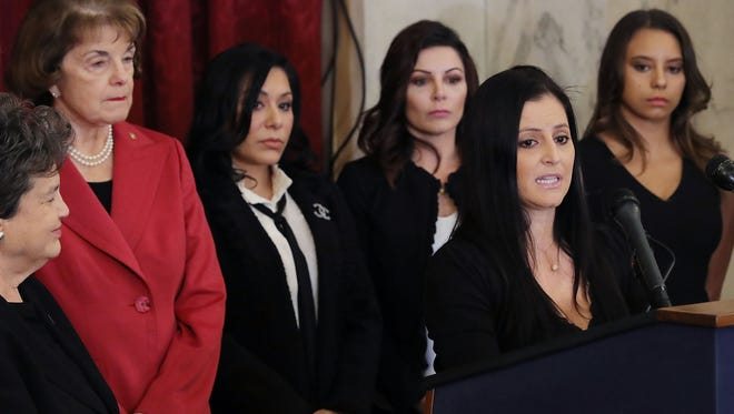 """U.S. Olympics gold medalist Dominique Moceanu speaks during a news conference to discuss new legislation to protect athletes with (2nd L-R) Sen. Dianne Feinstein (D-CA), and fellow gymnasts Jeanette Antolin, Jamie Dantzscher and Mattie Larson in the Russell Senate Office Building on Capitol Hill January 30, 2018 in Washington, DC. Along with the gymnasts, all of whom are survivors of sexual abuse at the hands of coaches or trainers, the members of Congress were confident that the legislation would pass and """"require amateur athletics governing bodies to immediately report sex-abuse allegations to law enforcement and strengthen oversight of gymnasiums, amateur sports organizations, and coaches."""""""