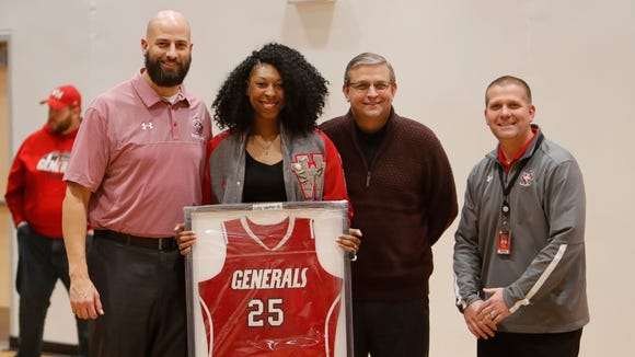 Former Wade Hampton basketball standout Alexis Dillard stands for a photo with, from left, Wade Hampton girls baasketball coach Eric Burrow, Greenville County athletic director Darryl Nance and Wade Hampton principal Eric Johnson after Dillard's jersey was retired Friday night.
