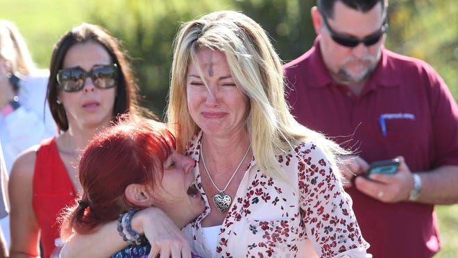 Parents wait for news after a report of a shooting at Marjory Stoneman Douglas High School in Parkland, Fla.