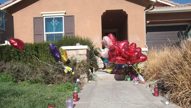 Candles and balloons stand outside a Perris, Calif., house where authorities say 13 siblings had been imprisoned by abusive parents David and Louise Turpin.