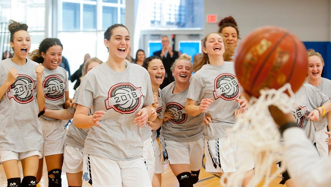 An elated Mercy Jaguars squad runs to collect its championship trophy, net and game ball in the Sixth Region girls basketball championship after defeating the North Bullitt Lady Eagles 64-46 to advance to the state Sweet 16. Saturday, March 3, 2018
