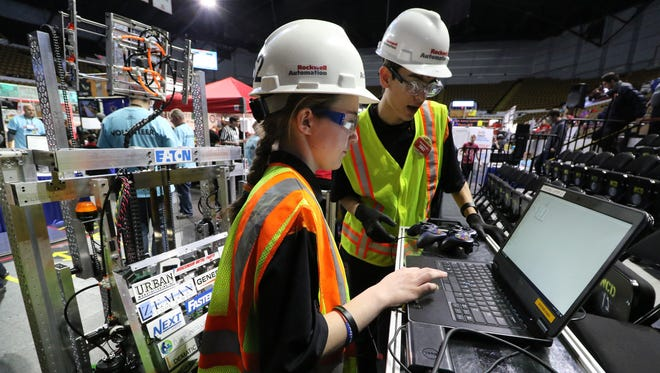 Katie Carroll and Andrew Kempen wait with the Waukesha CORE team's robot at last year's FIRST Robotics regional competition at the UW-Milwaukee Panther Arena. The robots, and the young people who build them, are back at the arena this weekend.