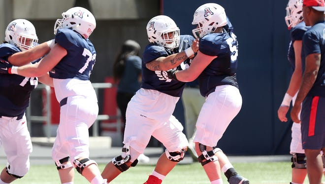 Arizona Wildcats offensive tackle Michael Eletise (75), center, runs drills during the Arizona Wildcats spring football scrimmage on April 7, 2018, at Arizona Stadium in Tucson, Ariz. The spring game is April 14 at 5 p.m.