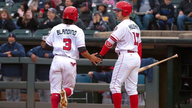 Louisville Bats Alex Blandino scores against the Toledo Mud Hens. At right is  Patrick Kivlehan, congratulating Blandino.