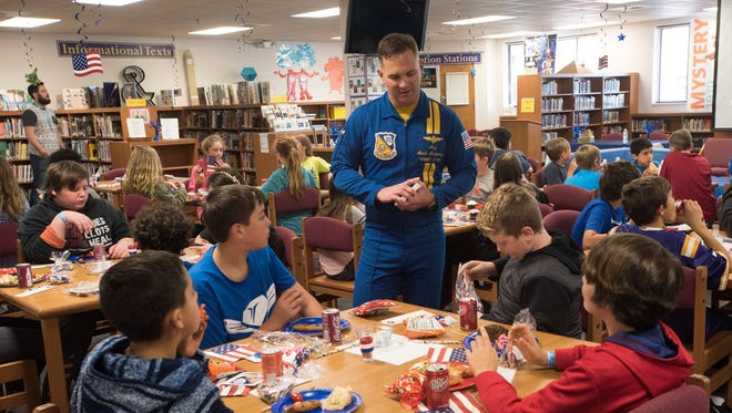 """Fat Albert pilot, Marine Corps Maj. Mark Montgomery, standing, talks with a group of sixth-graders at Gulf Breeze Middle School Friday, April 13, 2018. Montgomery spoke at the school as part of its """"Month on the Military Child"""" program."""