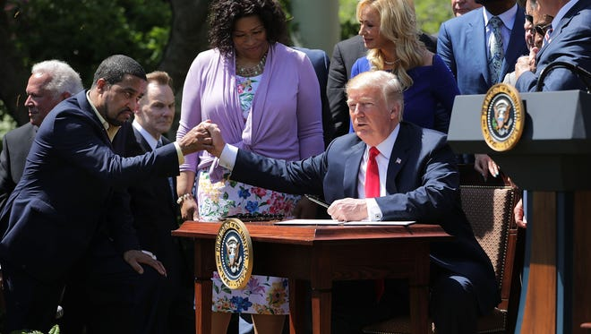 President Trump shakes hands with Pastor Darrell Scott, co-founder of the New Spirit Revival Center, before Trump signs an executive order during an event in the Rose Garden Thursday.