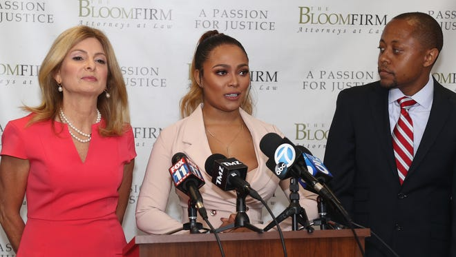 Teairra Mari, center, and her attorneys Lisa Bloom and Walter Mosely speak during a press conference about new legal action against rapper 50 Cent and Akbar Abdul-Ahad, Thursday, in Woodland Hills, Calif.  Mari's former boyfriend Abdul-Ahad allegedly posted a sexually explicit photo of her to her Instagram account after they broke up and 50 Cent reportedly reposted the image.