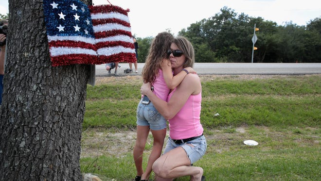 Carissa Potts hugs her 7-year-old daughter, Kaylee, after leaving flowers May 19, 2018, at a small memorial outside of Santa Fe High School in Santa Fe, Texas. The morning before, Dimitrios Pagourtzis, 17, entered the school with a shotgun and a pistol and opened fire, killing 10 people.