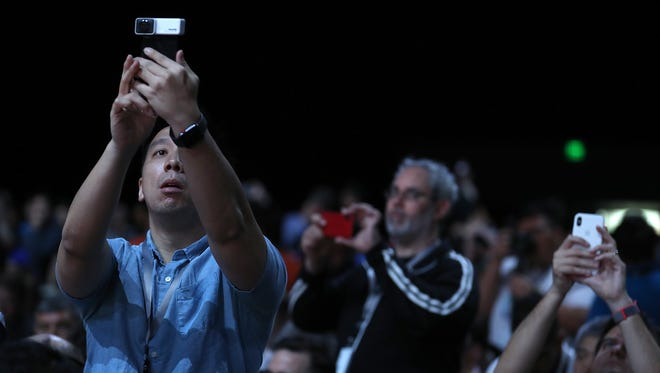 Attendees take pictures before the start of the opening keynote during the 2018 Apple Worldwide Developer Conference at the San Jose Convention Center on June 4, 2018 in San Jose, Calif. Apple CEO Tim Cook will kick off the WWDC that runs through June 8.