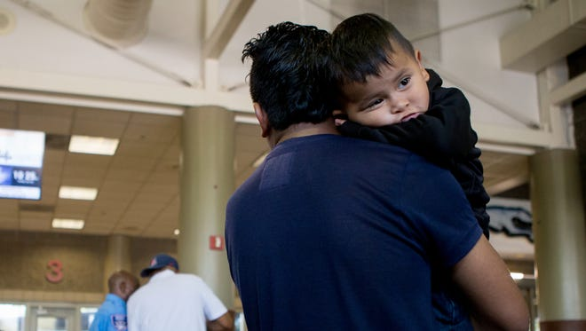 Edwin Antonio Gonzalez, 24, and his son Francisco, 2, both of Guatemala, wait to board their next bus after being released by the Department of Homeland Security on July 12, 2018, at a bus station in Phoenix.
