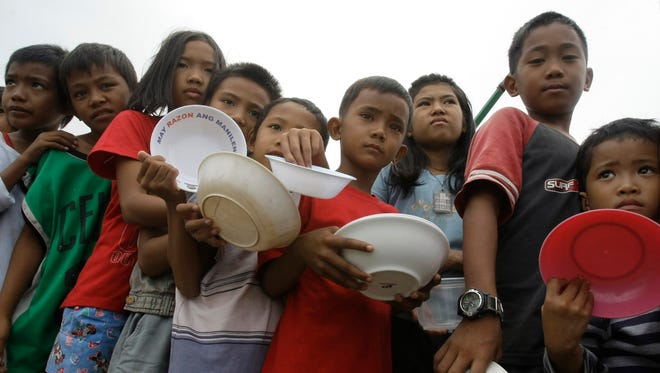 Children carrying bowls wait in line for a free porridge Saturday, Oct. 2, 2010 in Manila's depressed area of Baseco. President Benigno Aquino III expressed support for the right to contraception as proponents argued that rapid population and high fertility rates have exacerbated crushing poverty, and birth control could be a powerful way to raise living standards.