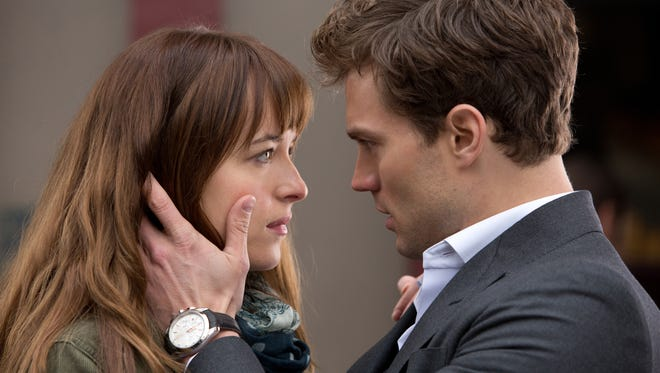 """In this image released by Universal Pictures and Focus Features, Dakota Johnson, left, and Jamie Dornan appear in a scene from the film, """"Fifty Shades of Grey."""""""