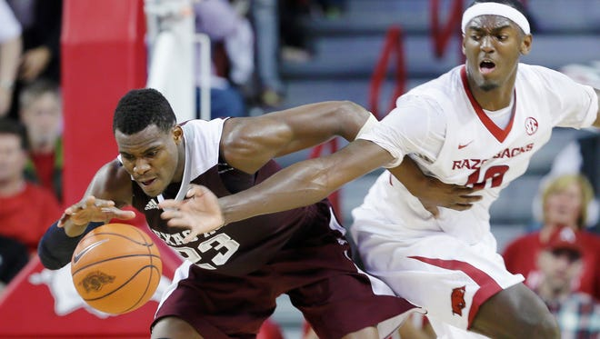 Arkansas' Bobby Portis (10) tries to slap the ball away from Texas A&M's Danuel House (23) during the second half of their SEC game in Fayetteville on Tuesday night. Arkansas won 81-75.