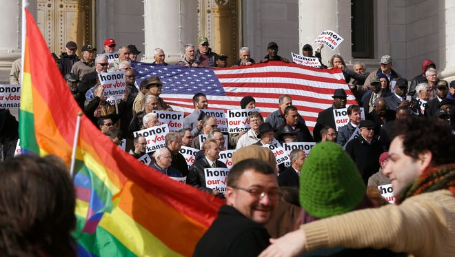 Supporters of Arkansas' law banning same-sex marriage, top, hold a rally at the Arkansas state Capitol in Little Rock, as protestors carry flags and shout Wednesday. Challenges to the ban are scheduled to go before two separate courts Thursday. The state Supreme Court plans to hear oral arguments in a lawsuit over the ban, hours before a federal judge holds a hearing on a separate lawsuit.