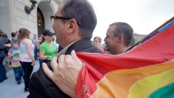 In this file photo taken May 12, 2014, Shon DeArmon, right, puts his arm around his partner James Porter while holding a flag outside the Pulaski County Courthouse in Little Rock.  A federal judge Tuesday struck down Arkansas' gay marriage ban which could pave the way for county clerks to resume issuing licenses to same-sex couples.