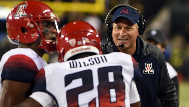 Arizona head coach Rich Rodriguez celebrates with running back Nick Wilson (28) after Wilson scored a touchdown during the third quarter of the NCAA college football game against Oregon at Autzen Stadium on Thursday, Oct. 2, 2014, in Eugene, Ore. Arizona won the game 31-24.