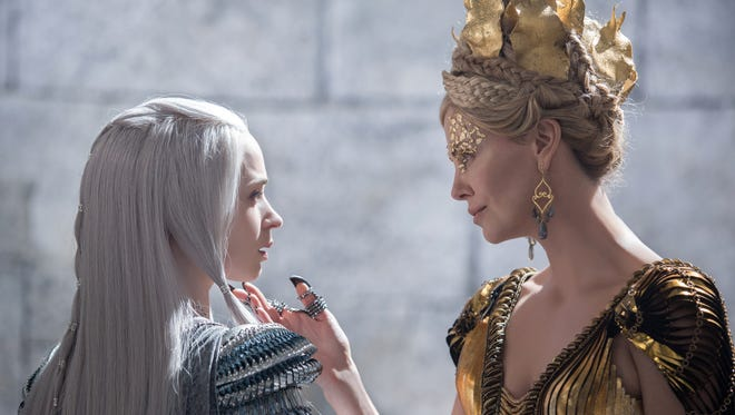 "In this image released by Universal Pictures, Emily Blunt, left and Charlize Theron appear in a scene from ""Huntsman: Winter's War."""