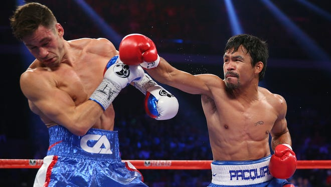 Manny Pacquiao of the Philippines and Chris Algieri of the United States exchange punches during the WBO world welterweight title at The Venetian on November 23, 2014 in Macau, Macau.