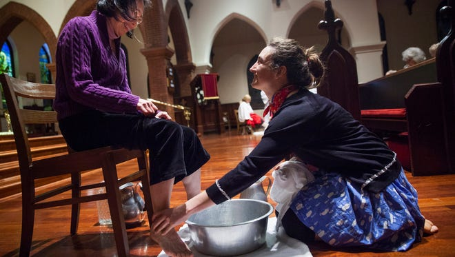 """Anne Paulus washes Misa Stuart's feet as part of the Maundy Thursday service at Trinity Episcopal Church in Staunton on Thursday. """"I was like, 'Oh dear,"""" and then I was like, 'Well that makes a lot of sense,'"""" said Paulus, describing her first thoughts after hearing they would be performing the ceremony she had never taken part in."""