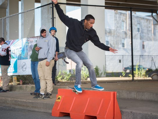 A skateboarder performs a trick in 2015 under I-95