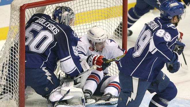 Amerks center Allan McPherson ends up in the Crunch net after goalie Kristers Gudlevskis stopped his shot during a first-period penalty kill.