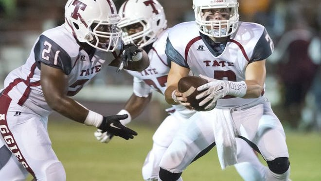 Tate High School running back Alondo Tompkins, (No. 23), left, prepares to take a hand-off from quarterback Sawyer Smith.