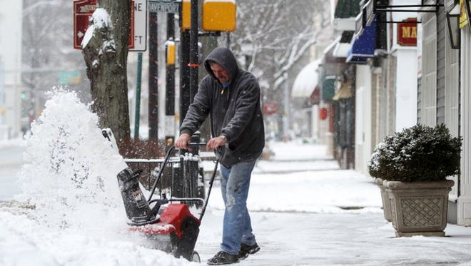 Cas Serafin uses a snow blower to clear the sidewalk in front of Lloyds Outlet, Tuesday, January 27, 2015, on West Main Street in Somerville, NJ.