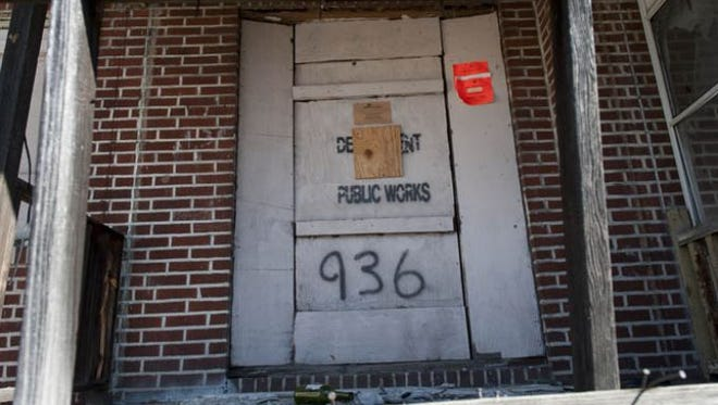 Orange signs and boarded-up doors are a familiar sight in certain Camden neighborhoods.
