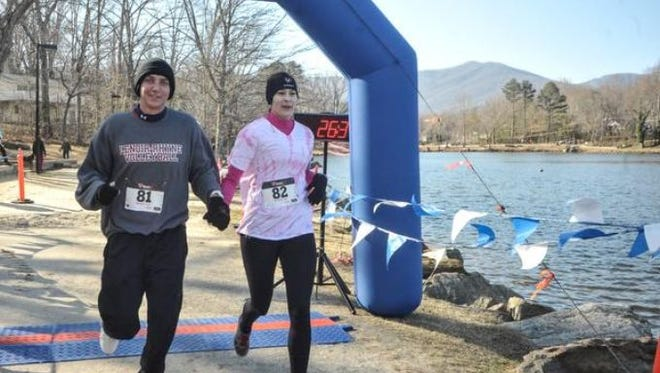 Anna Moore and Elliot Criss hold hands across the finish line at the annual Black Mountain Valentines 5k held this year, on Valentine's Day. They were the first of many couples finishing together.