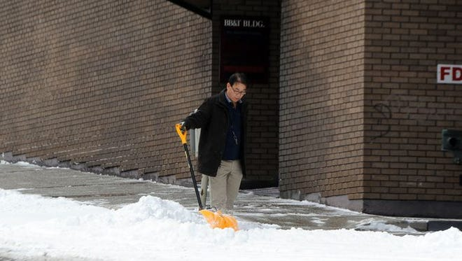 A man shovels snow along College Street in downtown Asheville Tuesday.