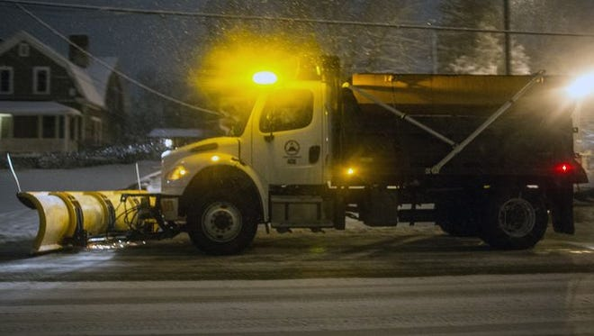 A city of Asheville vehicle plows snow early Thursday.