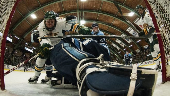 Catamounts forward Colin Markison (6) is knocked into the net by Blackbears defenseman Ben Hutton (10) during the Hockey East quarterfinal men's hockey game between the Maine Blackbears and the Vermont Catamounts at Gutterson Fieldhouse on Saturday night.