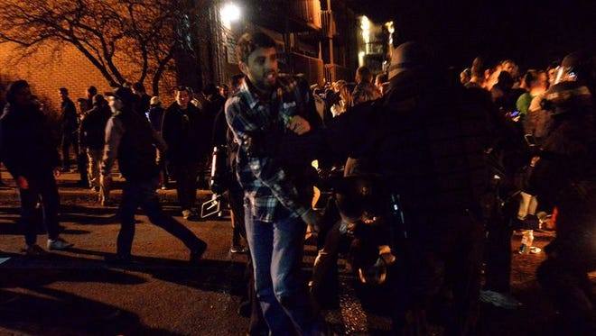 Police detain one person late Friday, March 27, 2015, after breaking up a crowd of revelers in the area known as Cedar Village in East Lansing. A crowd of a few hundred people gathered to celebrate Michigan State's Sweet 16 victory over Oklahoma.