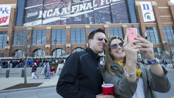 Bryan Callahan (left), and his wife Ashley Callahan, Zionsville, shoot a selfie outside of the NCAA Men's Basketball Final Four, Lucas Oil Stadium, Indianapolis, April, 4, 2015. They say they will hunt for a spot in a local sports bar to watch the games.