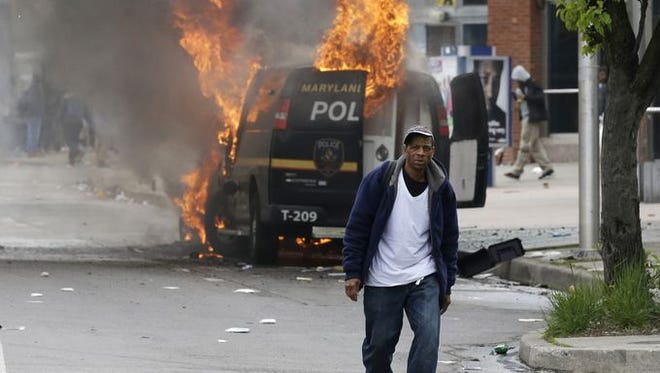 A man walks past a burning police vehicle in Baltimore.