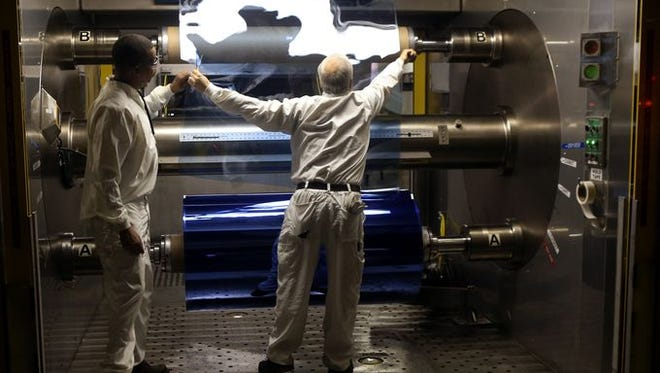 Tellis Paige and Dave Deisinger cut a roll of X-ray film made for Carestream off the ESTAR Manufacturing machine in Kodak's film-making operations at Eastman Business Park. The polyester roll, made from scratch in Building 317, can weigh up to 1,600 pounds.