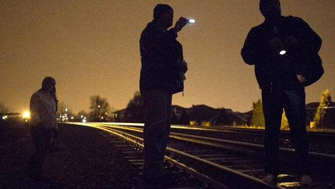 Jamason Bailey, right, Thomas Parmenter, center, and Jessica Achney search for homeless people living in the woods near the Baxter Ave. elevated train station during the Coalition for the Homeless' 2015 Louisville Metro Street Count.