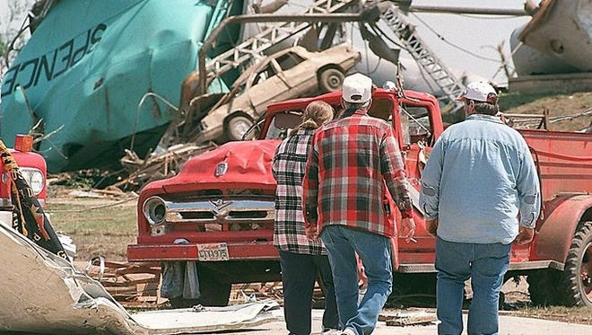 Spencer residents walk amid the destruction, which includes a firetruck and a twisted heap of metal made up mainly of the town's water tower.  Argus Leader file photo