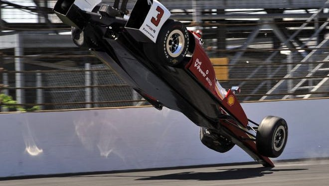 The car driven by Helio Castroneves, of Brazil, flips after hitting the wall in the first turn during practice for the Indianapolis 500 auto race at Indianapolis Motor Speedway in Indianapolis, Wednesday, May 13, 2015.
